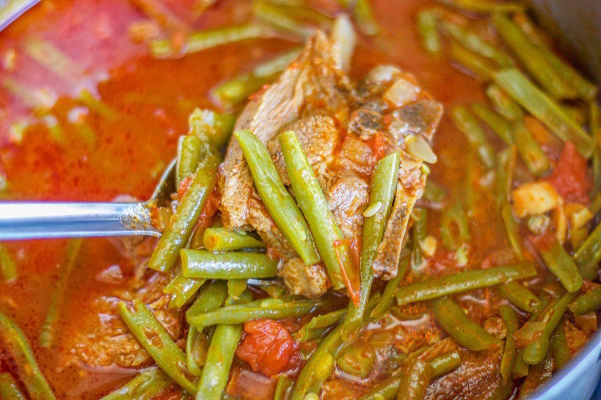 fasolia (bean stew) in a spoon over a pot
